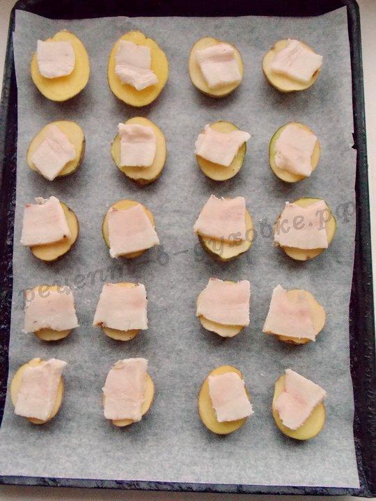 кладём на картофельные половинки ломтики сала