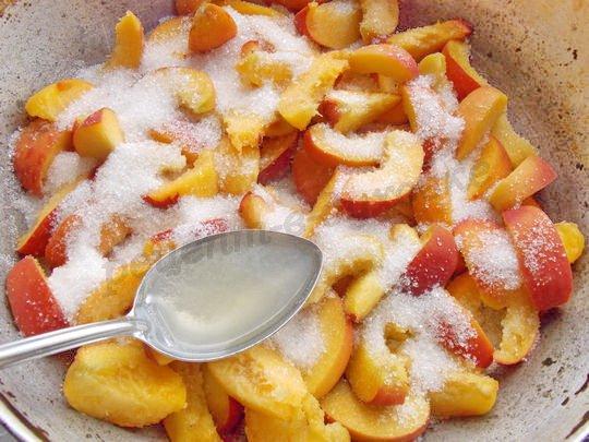 выкладываем кусочки персиков в форму, посыпаем сахаром и поливаем соком лимона