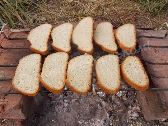 выкладываем ломтики хлеба на решётку над углями